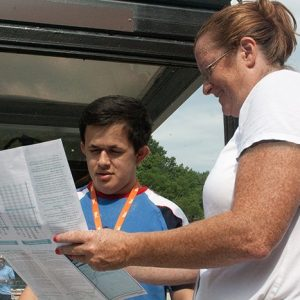 A female travel trainer shows a young man a transit system map. Working with PRTC, MTM created a sustainable travel training program that focuses on train the trainer training opportunities.