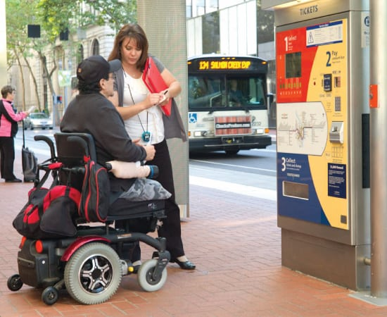 An MTM Transit assessor shows a man who utilizes a wheelchair how to use the TriMet bus. MTM Transit assessments help ensure LIFT paratransit eligibility for TriMet.