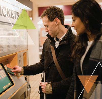 A man and woman stand at a ticket kiosk. The man is helping solve transit challenges for MTM Transit while ensuring every trip is important.
