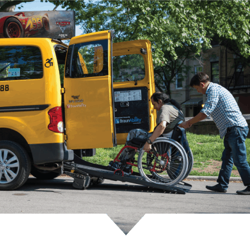 A TLC Accessible Dispatch driver helps a man who utilizes a wheelchair into his accessible taxi.