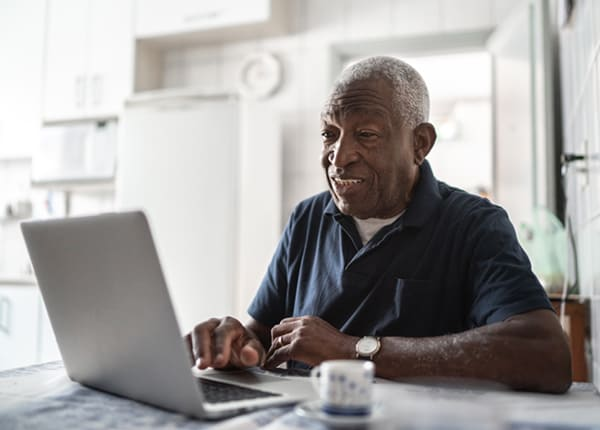 An older man sits behind his laptop using Mobility Direct, MTM Transit's online paratransit eligibility software that uses our remote ADA certification process.